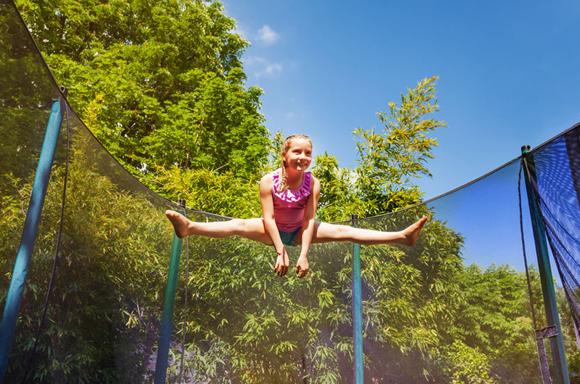 Low-angle portrait of preteen girl performing a split jump in the air, exercising on the trampoline outdoors