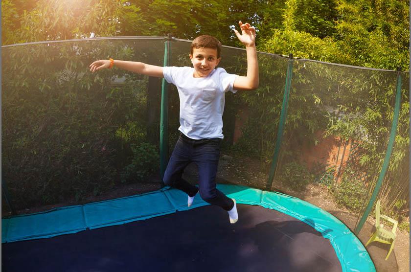 Portrait of preteen boy jumping high on the backyard trampoline in summer